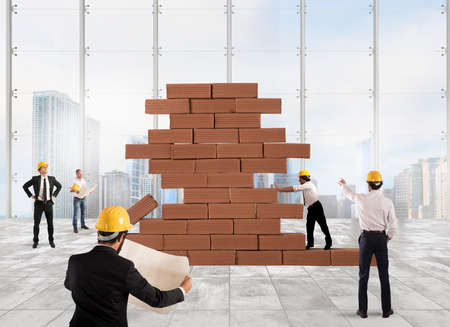 built: Team of architects working and analyzing on a bricks construction project