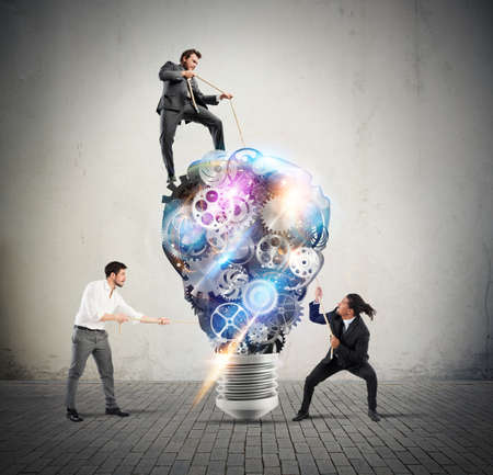 systems thinking: Teamwork of businesspeople work together to a lightbulb system of gears