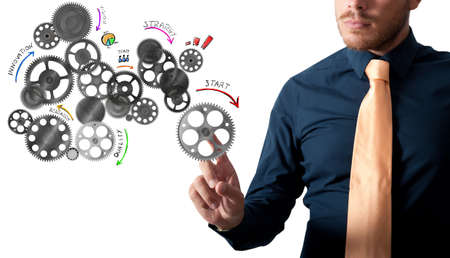 mechanisms: Businessman touching an analysis project with gear mechanisms designed Stock Photo