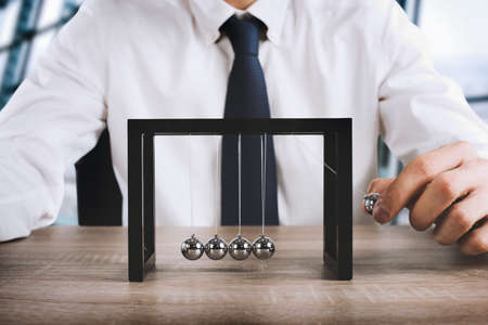 Businessman plays with the pendulum of Newtown balls