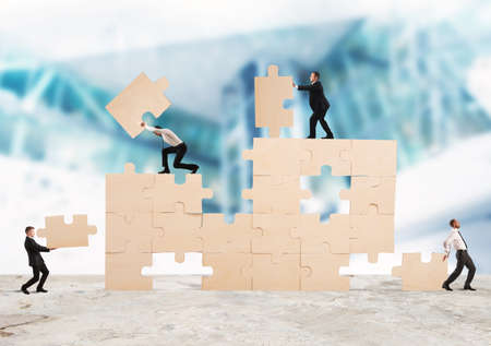 cooperate: Team of businessmen collaborate and cooperate to build a puzzle