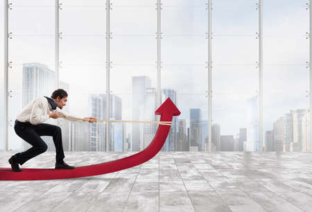 Determinated businessman with much effort lifts statistics arrow with a rope in a office