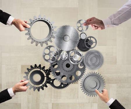 Teamwork der Geschäftsleute arbeiten zusammen und kombinieren Stücke von Zahnrädern zu einem mechanischen System