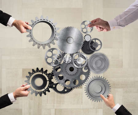 merging together: Teamwork of businesspeople work together and combine pieces of gears to a mechanical system