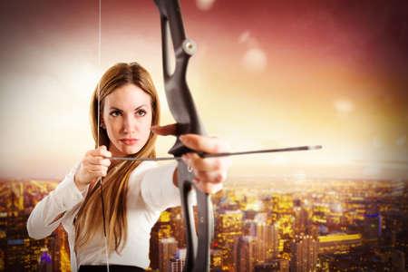 Empresaria con el arco y la flecha con la opinión del paisaje urbano