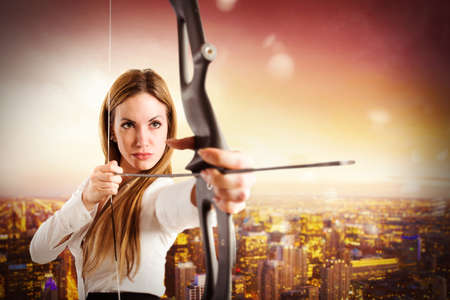 Imprenditrice con arco e freccia con vista sulla città