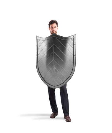 防衛: 盾を持ったビジネスマン。保護とビジネスの世界での防衛の概念 写真素材