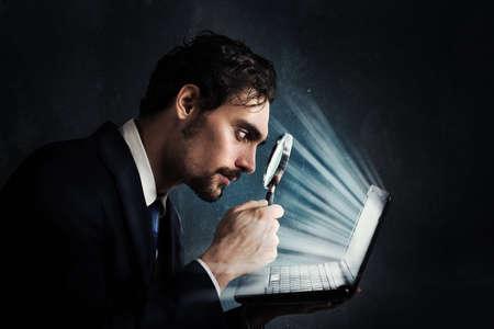 De zakenman kijkt met een vergrootglas naar het computerscherm