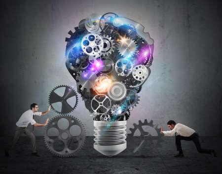 Business team push versnellingen in de richting van een grote gloeilamp. bouwen aan een idee concept Stockfoto