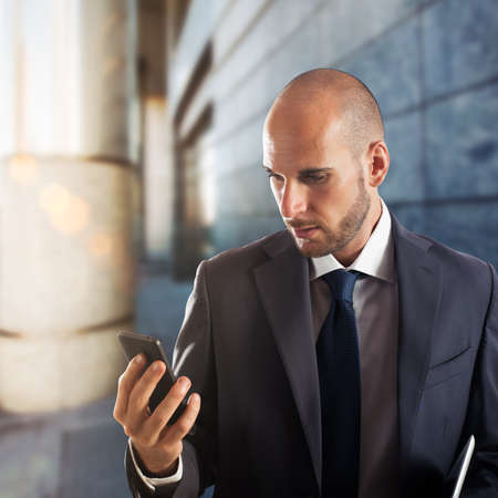 communication: Businessman touching cellphone screen with building in the background