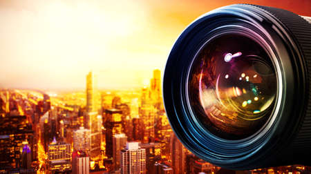 Professional lens of reflex camera with light effects and city on background