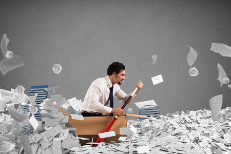 Concept of bureaucracy with man paddling in a sea of sheets Stockfoto