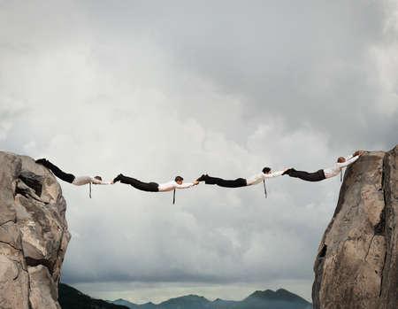 一緒に 2 つの山の間のブリッジを形成するビジネスマン 写真素材