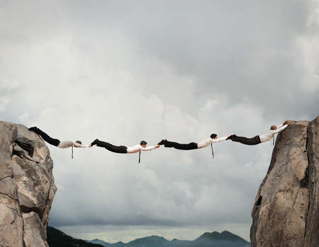 Los hombres de negocios que trabajan juntos para formar un puente entre dos montañas Foto de archivo - 64803693