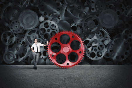 conjunction: Businessman builds a business system as a gears mechanism and puts the missing gear Stock Photo