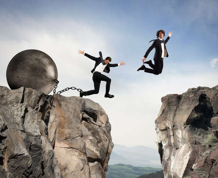 overcoming adversity: Man jumps between two mountains before the man with a heavy ball obstacle Stock Photo
