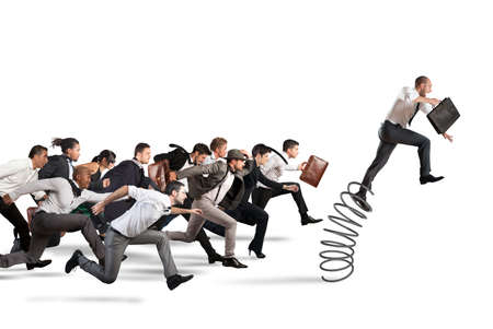 Businessman jumping on a spring during a race with opponents Stock Photo