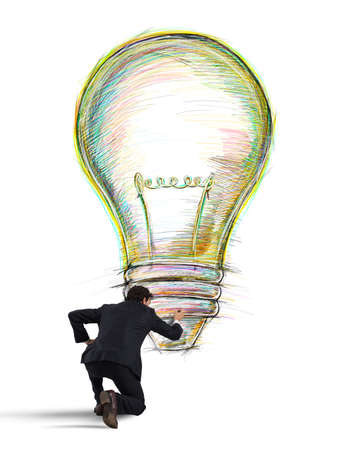 Businessman draws on the wall a big colored bulb with bright colors