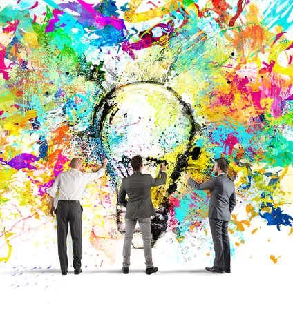 Bedrijfs persoon te schilderen samen een grote gekleurde gloeilamp op de muur