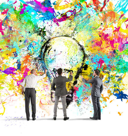 Business person paint together a big colored lightbulb on the wall Фото со стока - 64965990