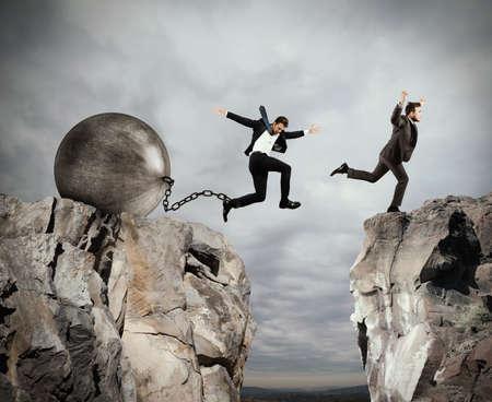 El hombre salta entre dos montañas antes de que el hombre con un obstáculo bola pesada Foto de archivo