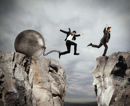 Man jumps between two mountains before the man with a heavy ball obstacle Stock Photo