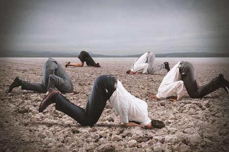 Uomini d'affari paura nascondono la testa sotto la terra come uno struzzo. La paura del concetto di crisi Archivio Fotografico - 64803708