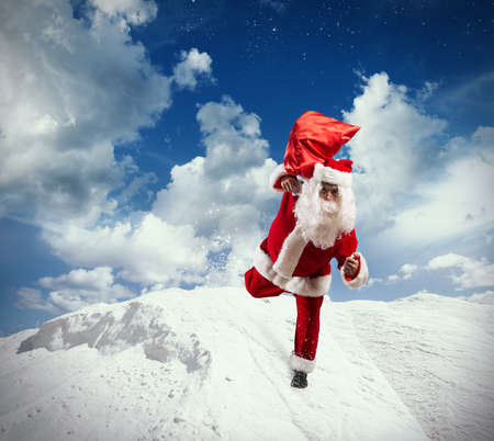 Santa Claus with gifts bag runs on the snow
