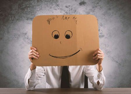 semblance: Businessman in the office holds a cardboard with a smiley face