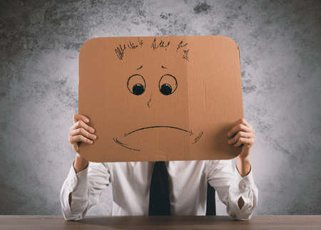 sorrowful: Businessman in the office holds a cardboard with a sad face