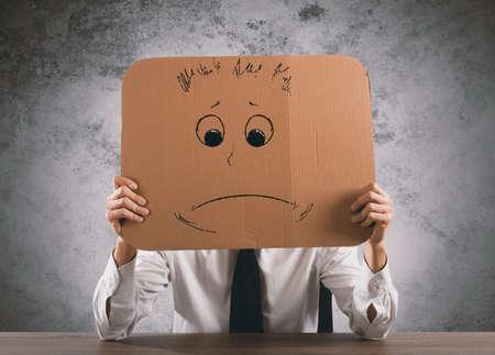 desconfianza: Hombre de negocios en la oficina tiene un cartón con una cara triste