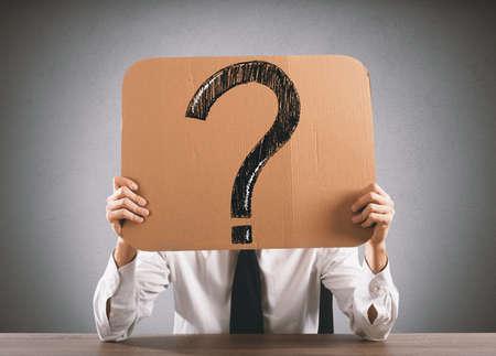 Zakenman in het bureau houdt een karton met groot vraagteken