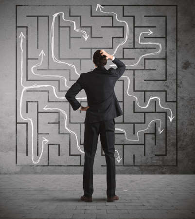 Confused business man seeks a solution to the labyrinth drawn on the wall