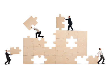 expertise: Team of businessmen collaborate and cooperate to build a puzzle