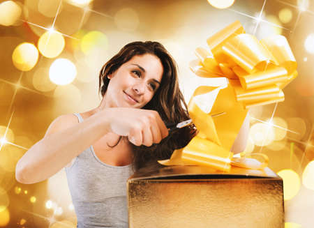 Girl prepare the bow of a big gift box on gold background