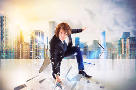 invincible: Business man punch with power and determination in the floor of roof Stock Photo