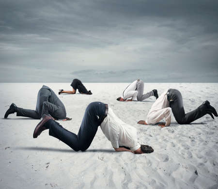 wimp: Afraid business people hide their head under the ground like an ostrich. Fear of crisis concept
