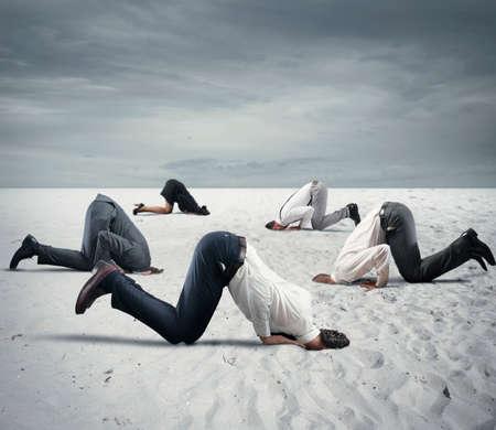 uomini d'affari paura nascondono la testa sotto la terra come uno struzzo. La paura del concetto di crisi