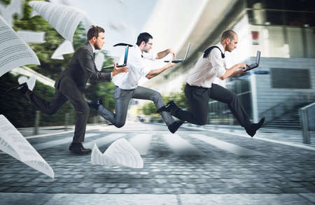 demanding: Businesspeople run on street to go to work with their laptop