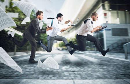 Ondernemers run op straat om te gaan werken met hun laptop Stockfoto
