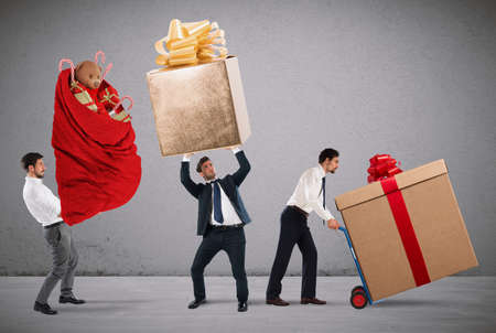 carrying: Businessmen pushes and holds heavy big gifts Stock Photo