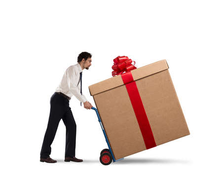 Businessman pushes heavy great gift with a cart Stockfoto - 132294130