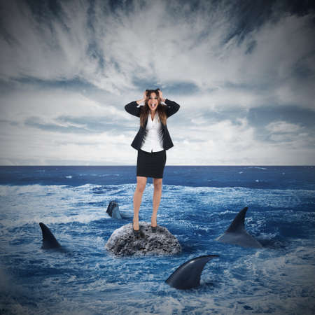 Businesswoman yelling on a rock surrounded by sharks