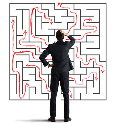 seeks: Confused business man seeks a solution to the labyrinth drawn on the wall