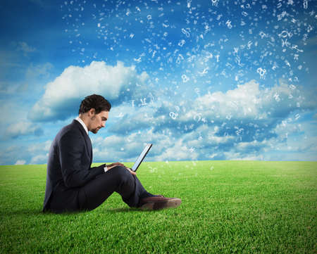 Businessman sitting on a lawn of grass. Internet and social network concept Stock Photo