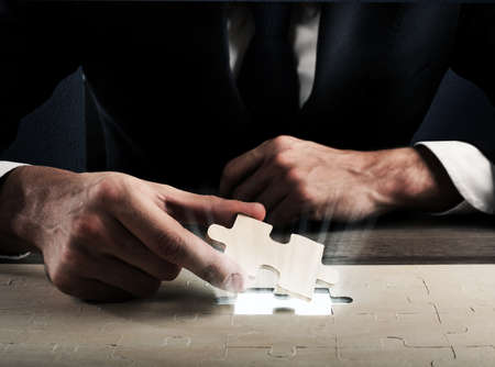 Businessman complete a puzzle inserting last piece Stock fotó