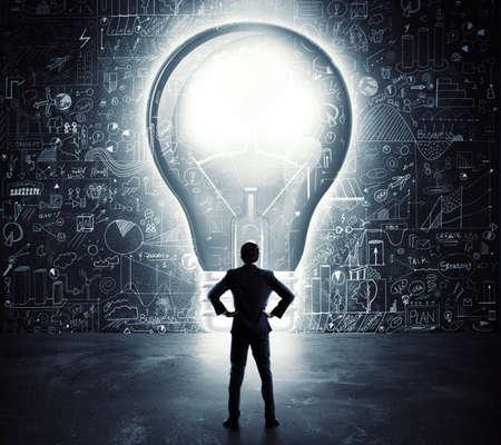 tecla enter: Hombre de negocios mira un gran agujero en la forma de una bombilla de luz en la pared