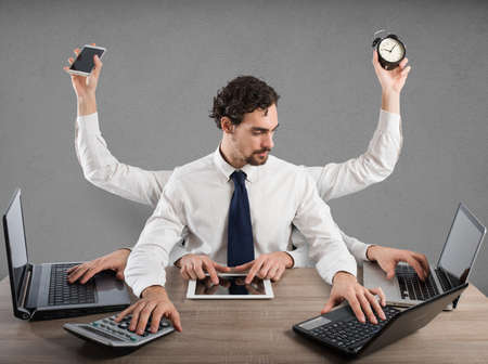 Businessman stressed by too many tasks works in the office 版權商用圖片