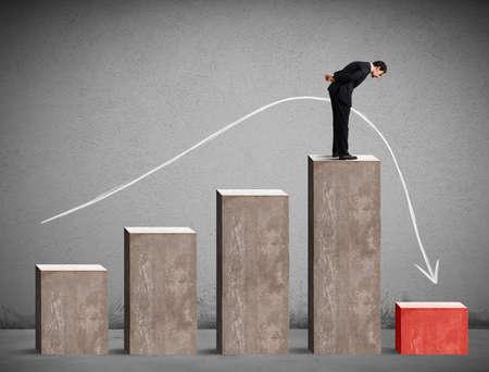 Homme d'affaires regardant vers le bas les performances des statistiques de façon drastique