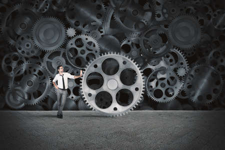 machine man: Businessman builds a business system as a gears mechanism and puts the missing gear Stock Photo